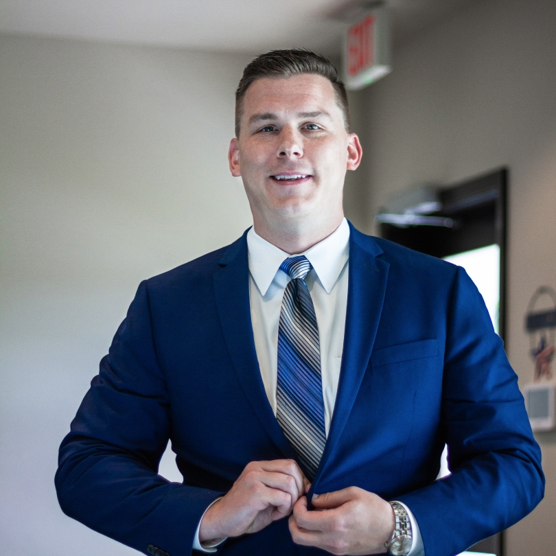 Attorney Evan Horner, from Carrollton, Texas, is smiling while buttoning his suit jacket.