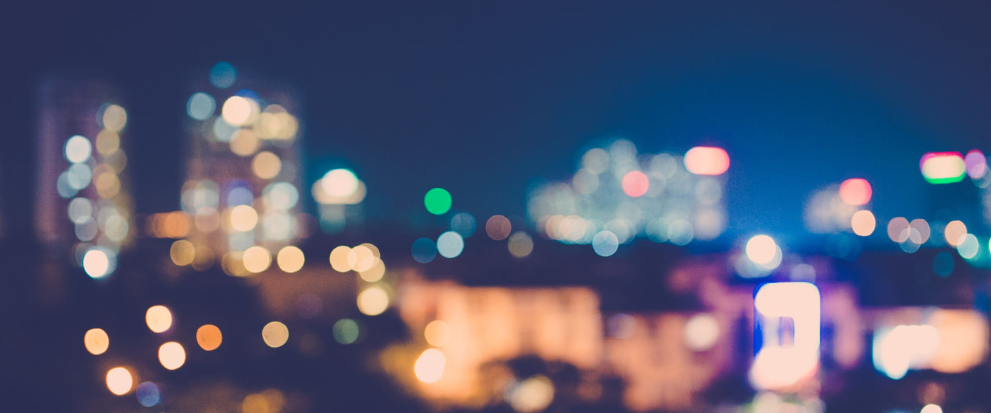 Blurred view of a city skyline at night.